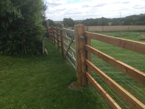 Commercial fencing and gate on a farm in Birmingham. A post and rail style perfect for housing livestock.