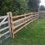 Commercial fence and gate surrounding a field. The fence is of a post and rail style perfect for a rural look.