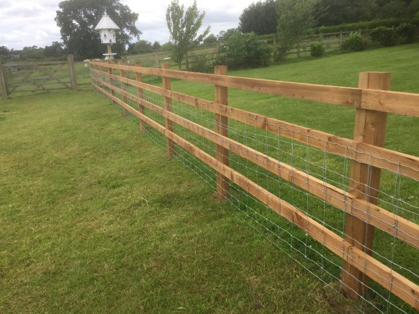 Post and rail fencing and gate in a empty field. The perfect commercial fencing for housing livestock.