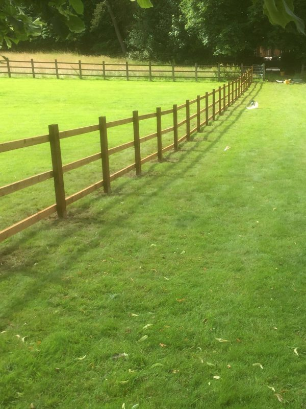 Post and rail fencing in a empty field in Birmingham.
