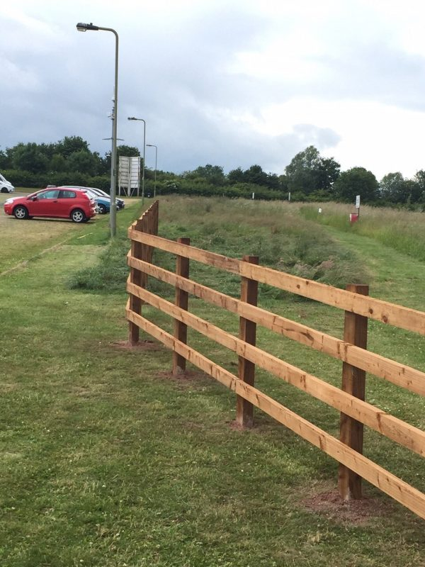 Commercial fencing with a red and blue car parked in front.