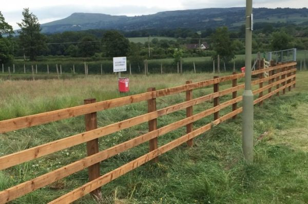 Post and rail fencing used for commercial purposes. Fencing stands alone in a empty field in Birmingham.