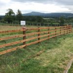 Post and rail fencing standing in a empty field. Commercial fencing perfect for securing livestock.