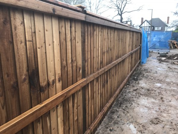 Wooden fencing being assembled in a building area. The paling fencing is perfect for securing the new properties being built.
