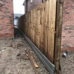 Newly assembled wooden garden fencing between two houses under construction.