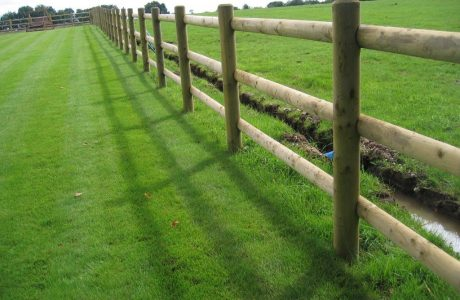 Round wooden fence posts and rails on a green field. Perfect for commercial fencing needs.