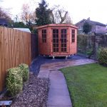 Made to measure garden shed standing in a long garden. This bespoke shed is hexagonal in shape.