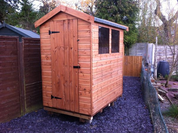 Made to measure garden shed stood in a garden with a gravel ground. The bespoke shed has two glass windows and a door.