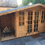 Made to measure garden shed standing in a yard beside a wall of ivory. This bespoke shed has glass windows and doors.