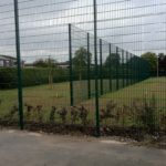 Green commercial fencing surrounding a sporting arena.