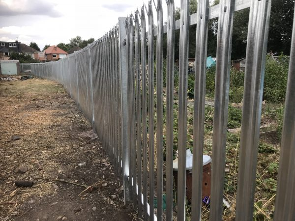 Steel commercial fencing surrounding deserted area. The steel commercial fencing is perfect for security purposes.
