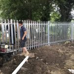 Steel commercial fencing being installed by three Hodges & Lawrence staff members in an outdoor space in Birmingham.