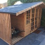 Made to measure garden shed in a garden. This bespoke shed has a slate roof and a log store on the side.