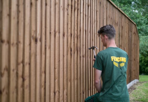 A Hodges & Lawrence staff member assembling a wooden fence in Birmingham.