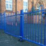 A blue steel commercial gate on a school yard in Birmingham.
