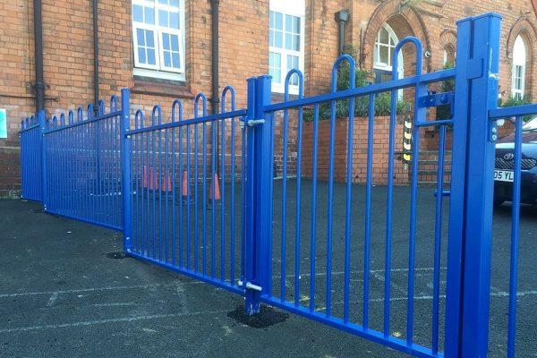 A blue steel commercial gate on a school yard in Birmingham.