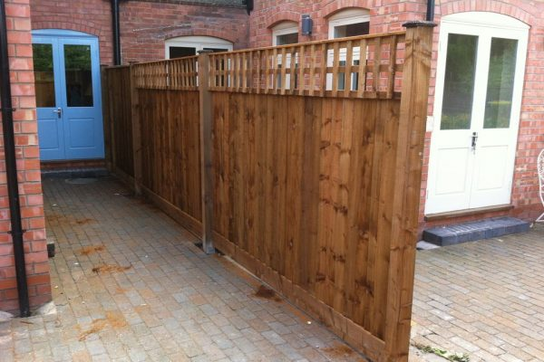 Wooden fencing outside of a house in Birmingham. The wooden fence panels are vertical with timber posts between.