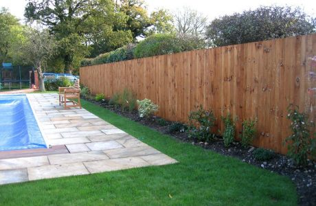 A garden in Birmingham with a pool. The garden is surrounded by a wooden feather edged fence.
