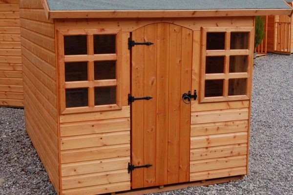 Made to measure garden shed standing in a garden. This bespoke shed has two windows and a door.