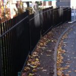 Commercial steel fencing surrounding a building situated next to a road.