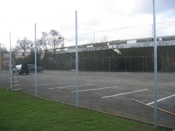 Chan link fencing. The commercial fence surrounds a car park containing two parked cars.