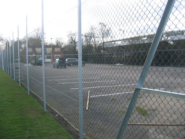 Chain linking fence surrounding a car park. This commercial fence provides security to the cars inside.