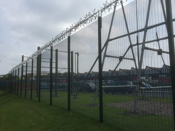 Green double mesh fencing with security spikes. This commercial fencing solution is perfect for security purposes.