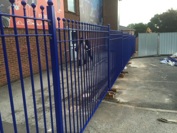 Blue bespoke railings surround a commercial or industrial building.