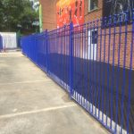 Blue bespoke railings stand in front of a commercial building.