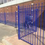 Blue bespoke railings surrounds a commercial area.