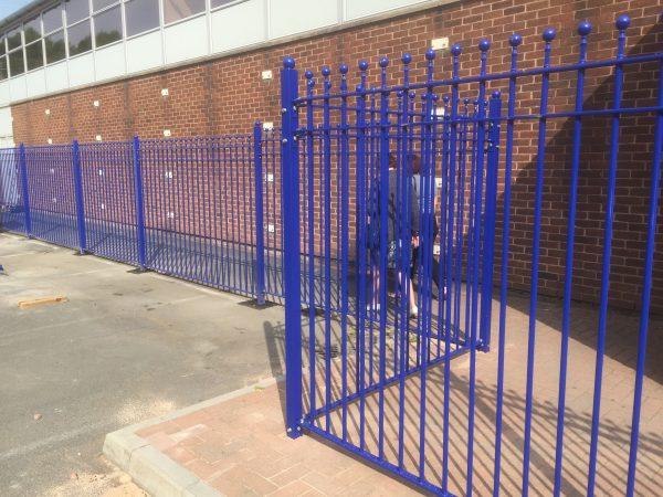 Blue bespoke railings surrounds a commercial area.