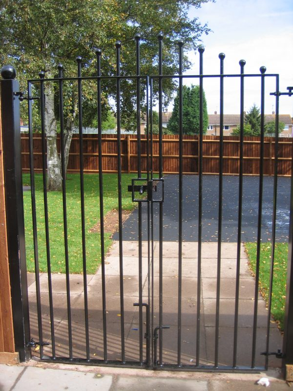 Black vertical bar steel gates. Locked and securing a garden.