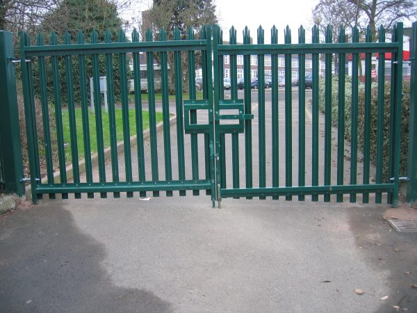 Green steel palisade gates stand in front of an school. These commercial gates provide security for the school.
