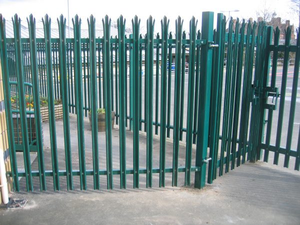 Green steel palisade fencing providing security for a commercial buildings in Birmingham.