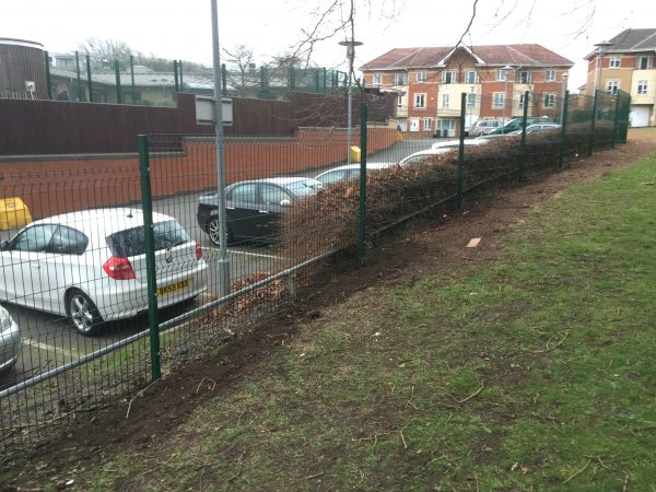 Mesh fencing panels standing in front of parked cars. These commercial gates offer security for private areas.
