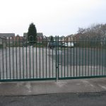 Green steel palisade gates stand in front of an empty yard. These commercial gates are perfect for securing school yards.