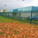 Green steel palisade fencing installed around a car park. Commercial fencing securely protects cars inside the car park.
