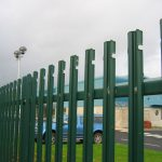 Green steel palisade fencing. This commercial fence is providing security for cars inside a car park.