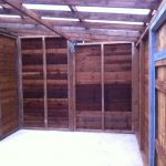 Inside of a commercial shed. The shed is wooden with a blue rope hanging from a roofing panel.