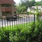 Black bespoke railings outside of a large house.