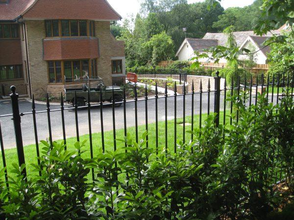 Black bespoke railings outside of a large house.