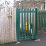 Green palisade gates attached to a wooden fence surrounding a school yard. Commercial gates and fencing great for security.