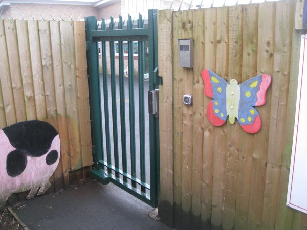 A green steel palisade gate securing a school yard.