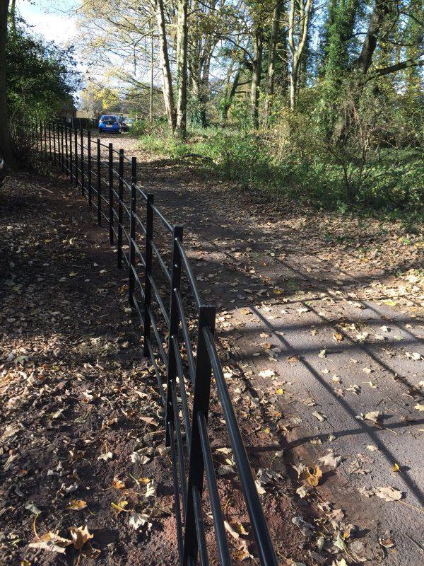 Black bespoke railings alongside a public walkway.