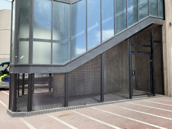 Double mesh fencing surrounding a commercial building. The commercial fence offers security for businesses and institutions.