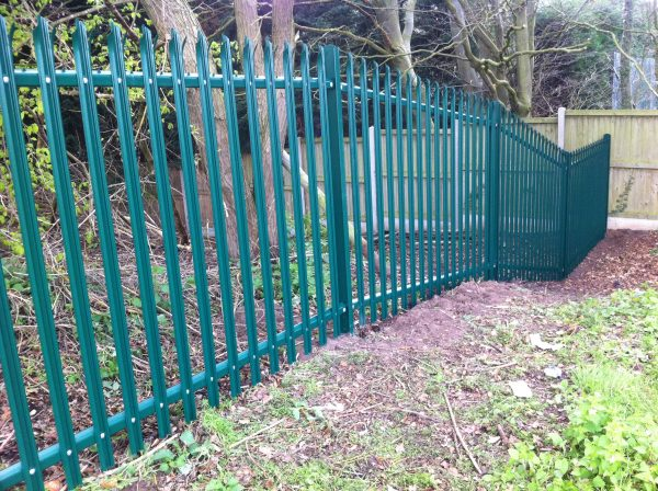 Green steel palisade fencing providing security for a private area in Birmingham.