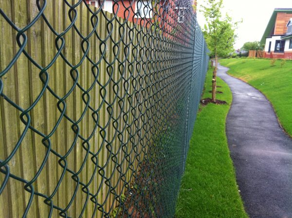 Green chain linking fence alongside a public walkway. Commercial fencing provides security for many different areas.