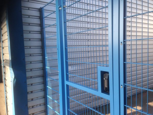 Blue double wire mesh gates, closed with secure locking system. These commercial gates are great at securing industrial areas