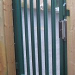 Green steel palisade gate securing a school yard.