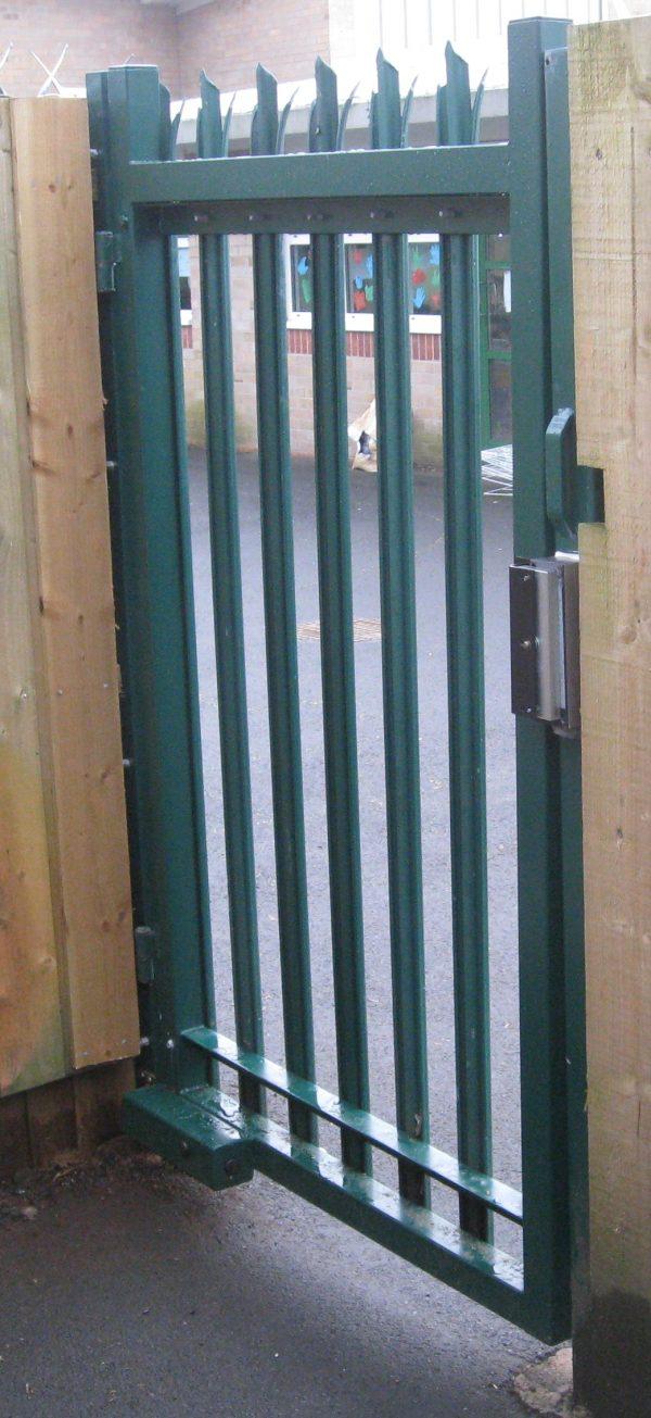 Green steel palisade gate securing a school yard.